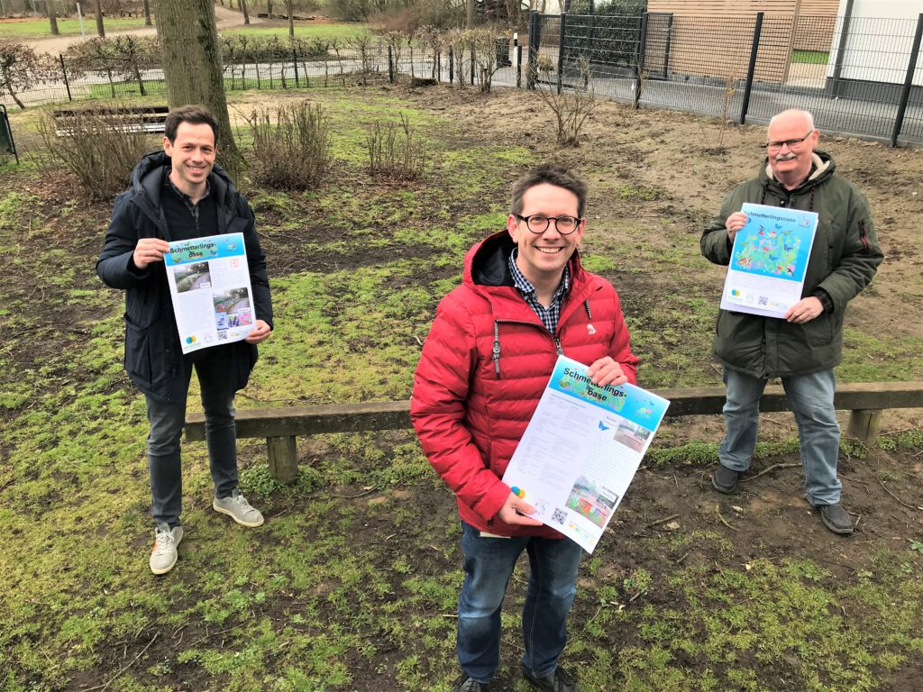 3 Männer halten Schilder zur Umgestaltung des alten Spielplatzes